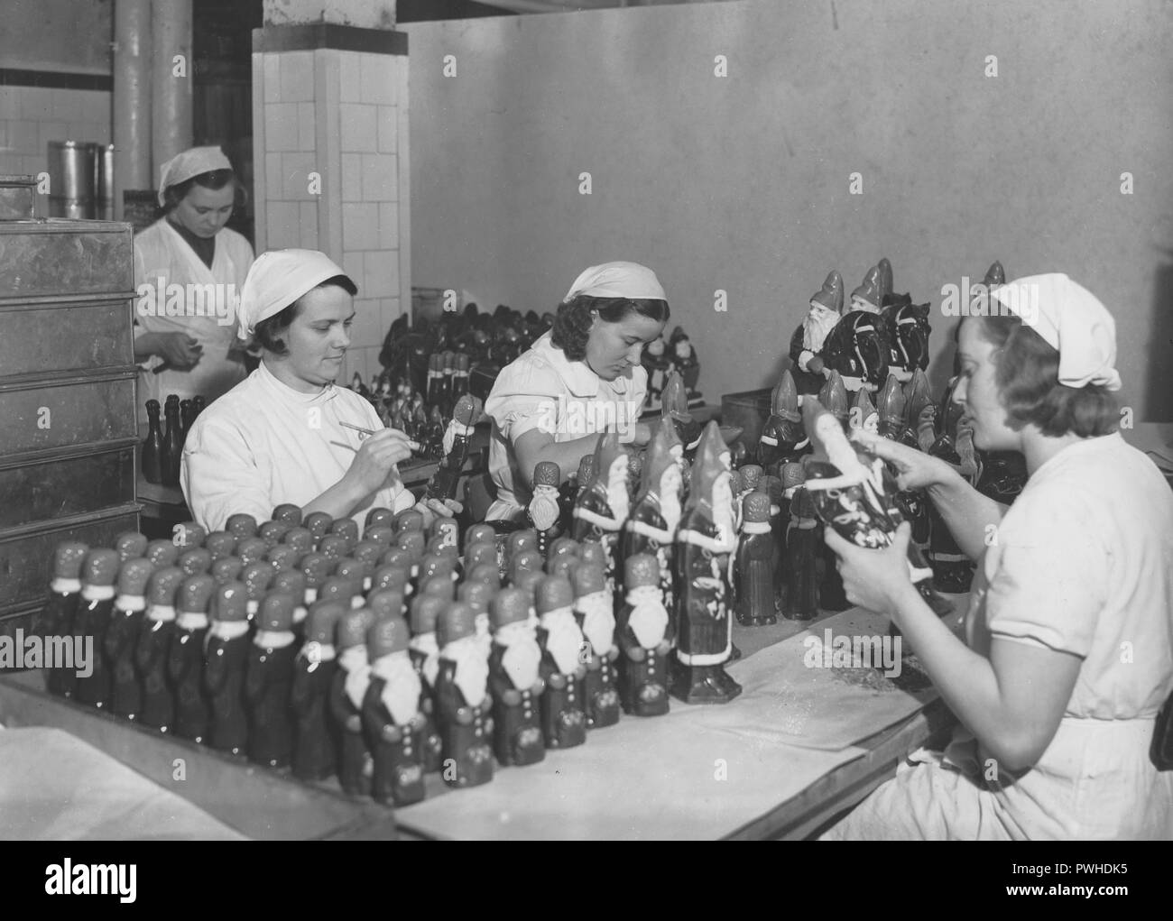 Christmas chokolate. Three young employees in the factory of the swedish chocolate maker company Cloetta. They are busy finishing the chocolate santa clauses that needs to be delivered to the stores. Cloetta company was established 1872 and was first to make chocolate products in an industrial environment. Sweden 1940s - Stock Image