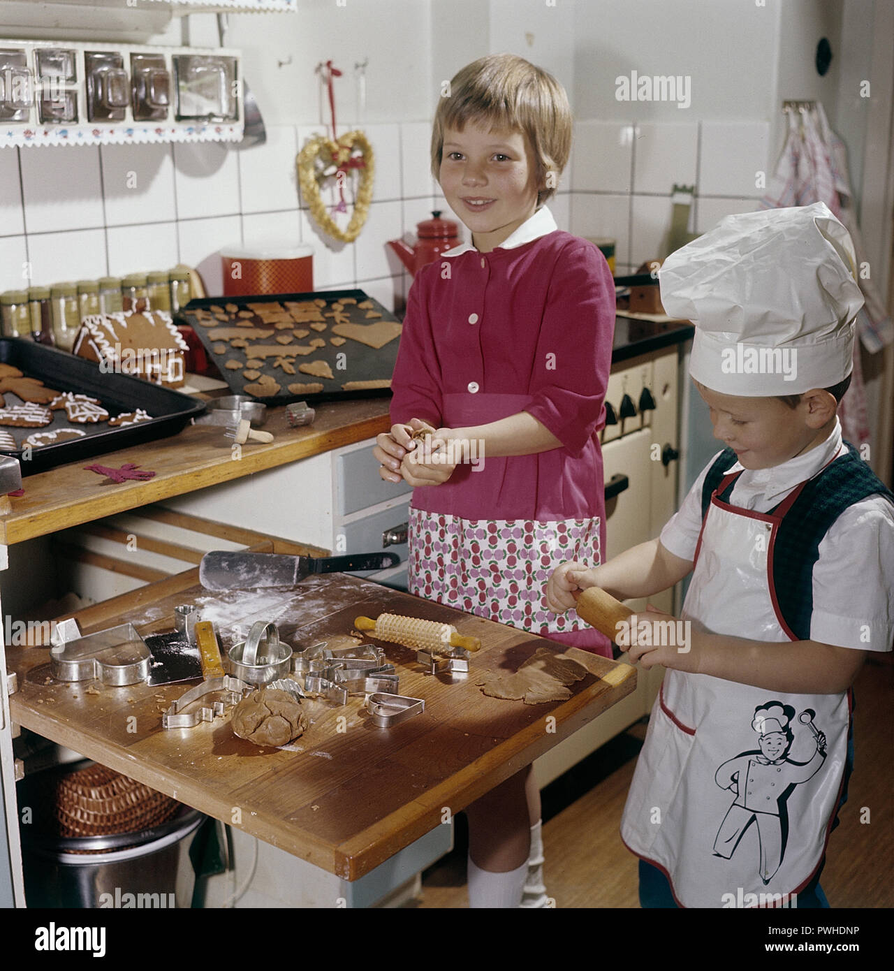 Christmas in the 1950s. A girl and a boy is busy in the kitchen baking ginger bread. With different shaped forms they get cakes as hearts and animals. Sweden 1950s. Ref BV86-10 - Stock Image