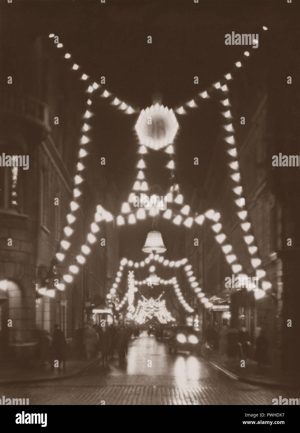 Christmas in the 1930s. The busy street Biblioteksgatan is decorated with christmas lights. The electric lights and the christmas decorations creates a nice christmas spirit. Sweden 1930s - Stock Image