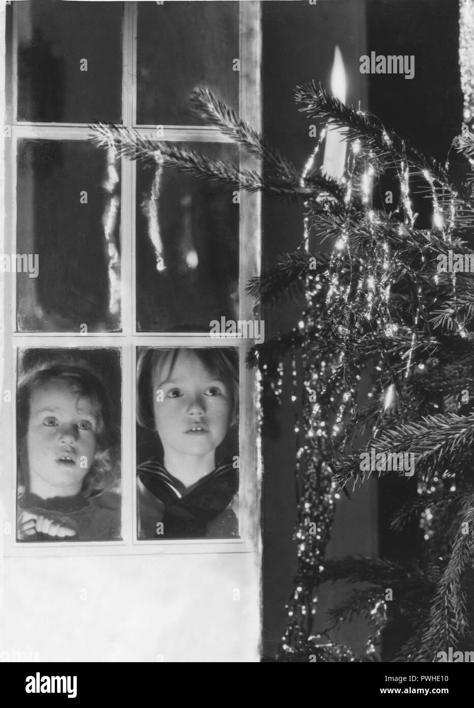Christmas in the 1940s. Two children are looking at the christmas tree at christmas eve. Sweden 1940s - Stock Image