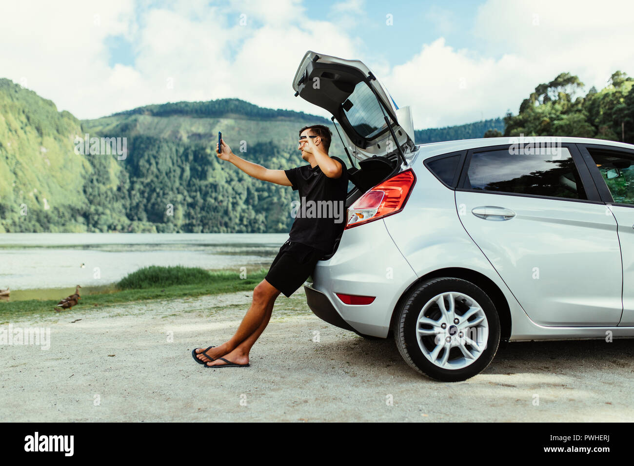 Young man sits in the car trunk take selfie photo on phone near beauty lake background. Summer vocation - Stock Image
