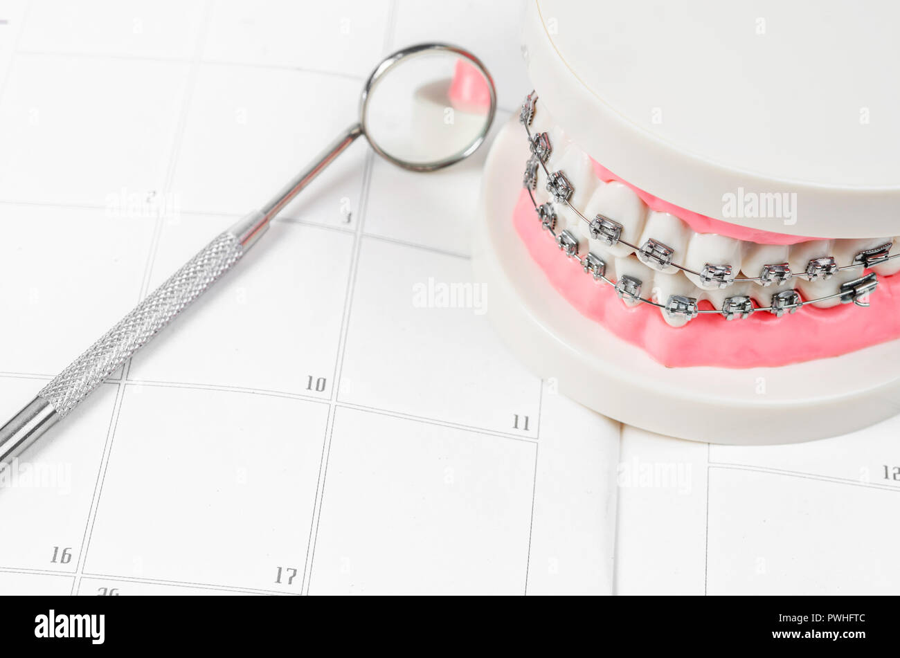 Tooth model with metal wire dental braces on a calendar. Regular checkups are essential to oral health - Stock Image