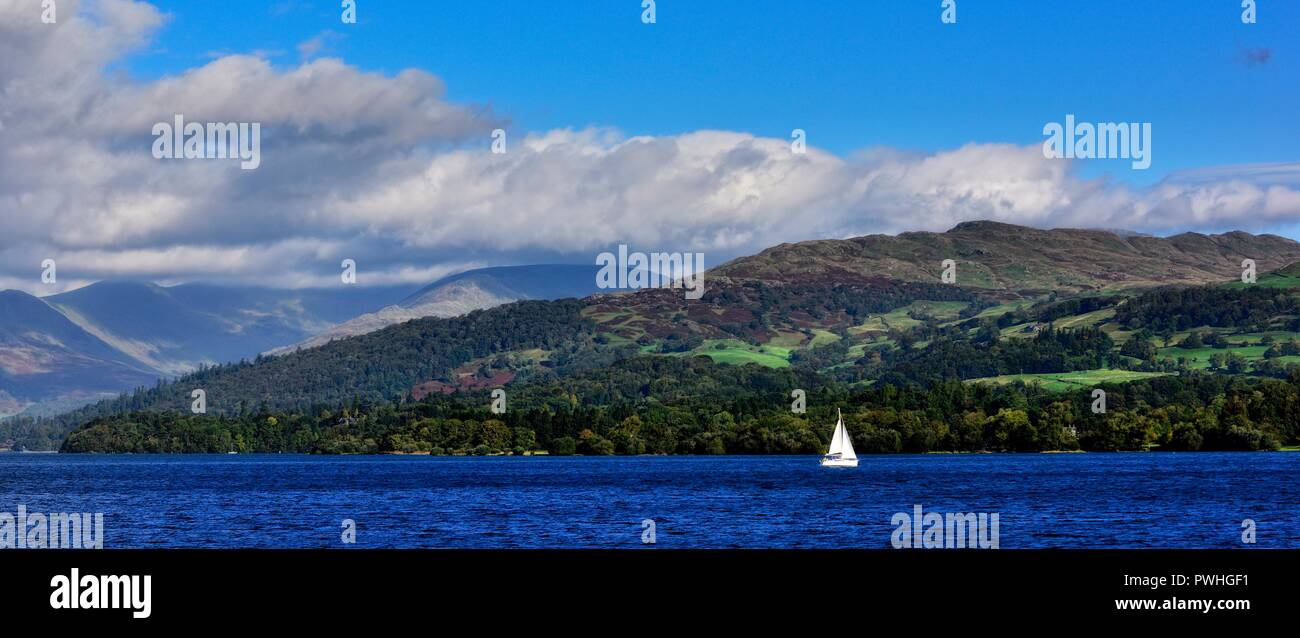 A small yacht dwarfed by the lake district scenery on lake Windermere,Cumbria,England,UK - Stock Image