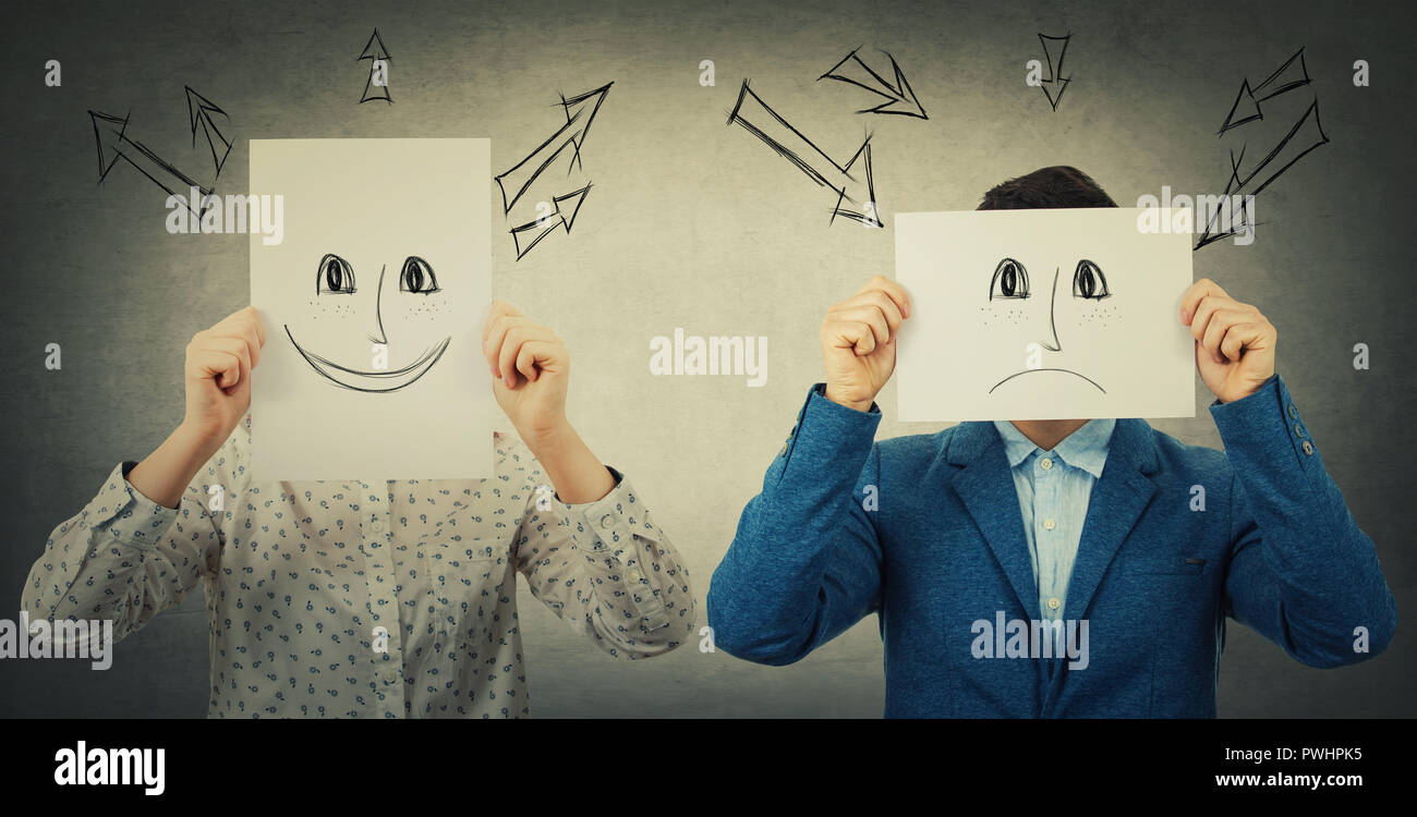 Businessman and businesswoman covering their faces using sheets with drawn happy and sad emoticons, like a mask to hide her real emotion from society. - Stock Image