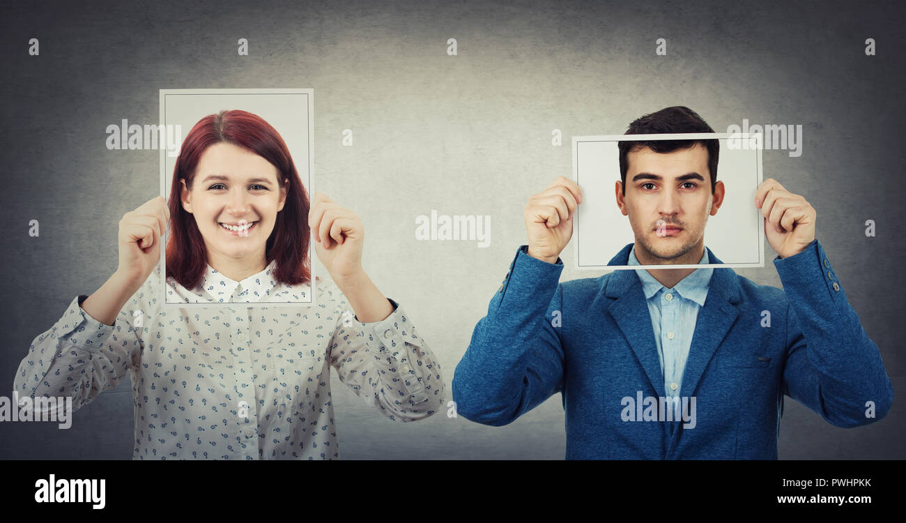Businessman and woman covering their faces using photo sheets with happy and sad portrait emoticon, like a mask to hide the real emotion from society. - Stock Image