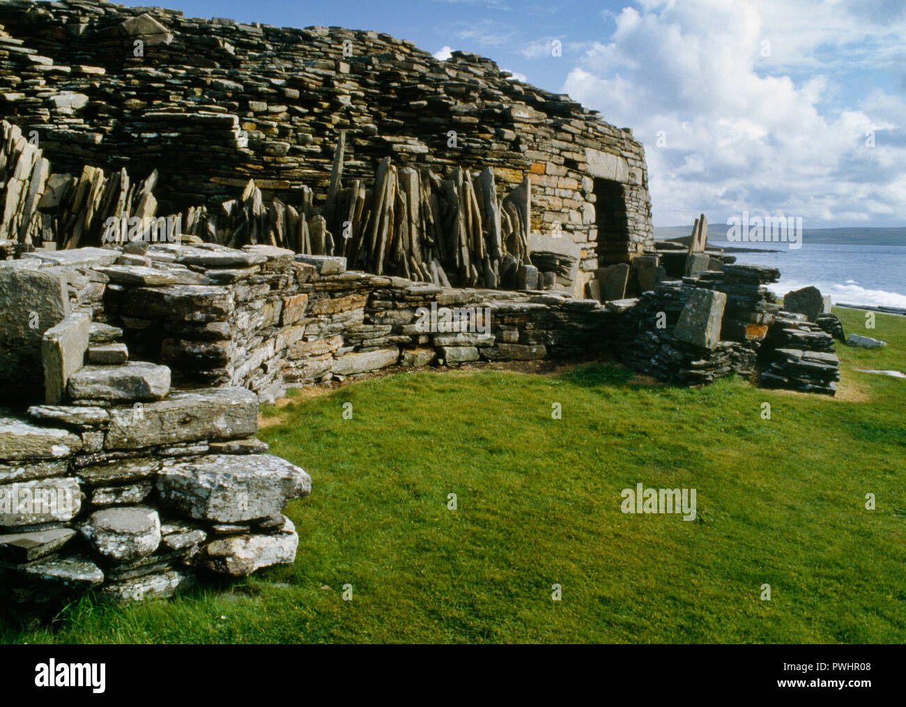 View SSE of the entrance to Midhowe Iron Age broch on the SW coast of Rousay island overlooking Eynhallow Sound & Orkney Mainland, Scotland, UK. - Stock Image