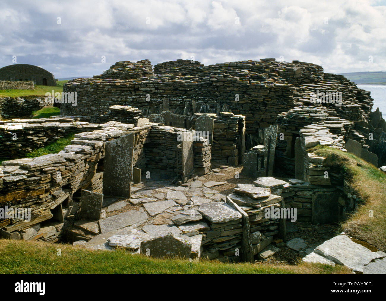 View S of later houses built around Midhowe Iron Age broch tower (rear centre) on the SW coast of Rousay island, Orkney, Scotland, UK. - Stock Image