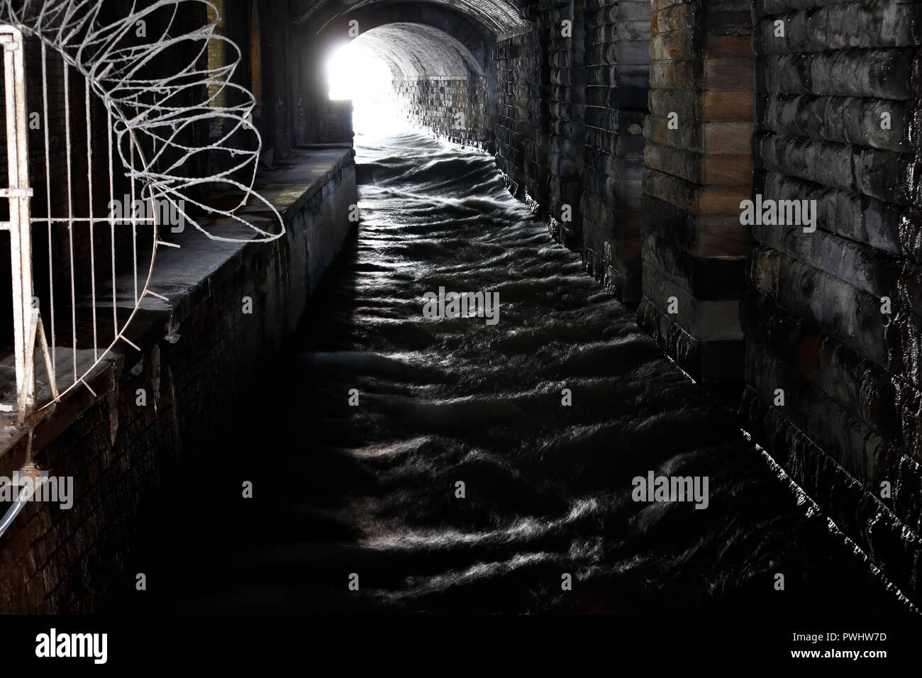 Tunnels beneath Leeds Railway Station with the River Aire running through , known as the Dark Arches. Stock Photo