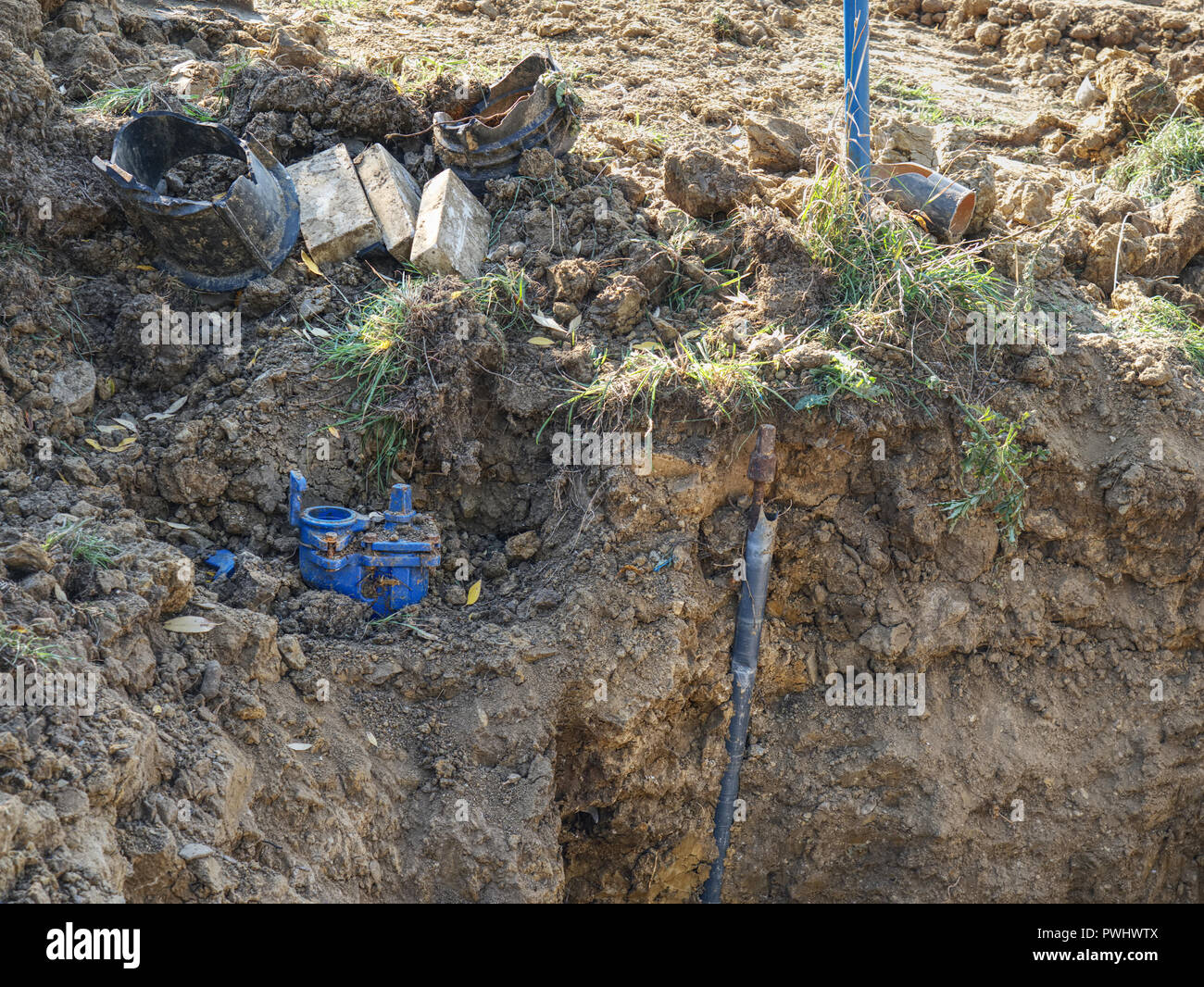 Plastic tubes in trench of sand joined together with press reduction member. Portable water supply chain in city. - Stock Image