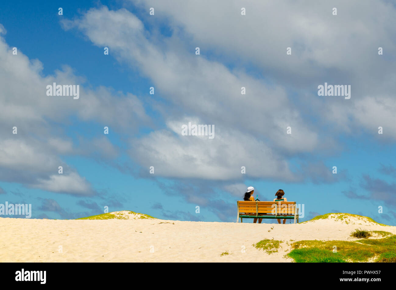 Two girls sitting on a bank in the beach - Stock Image