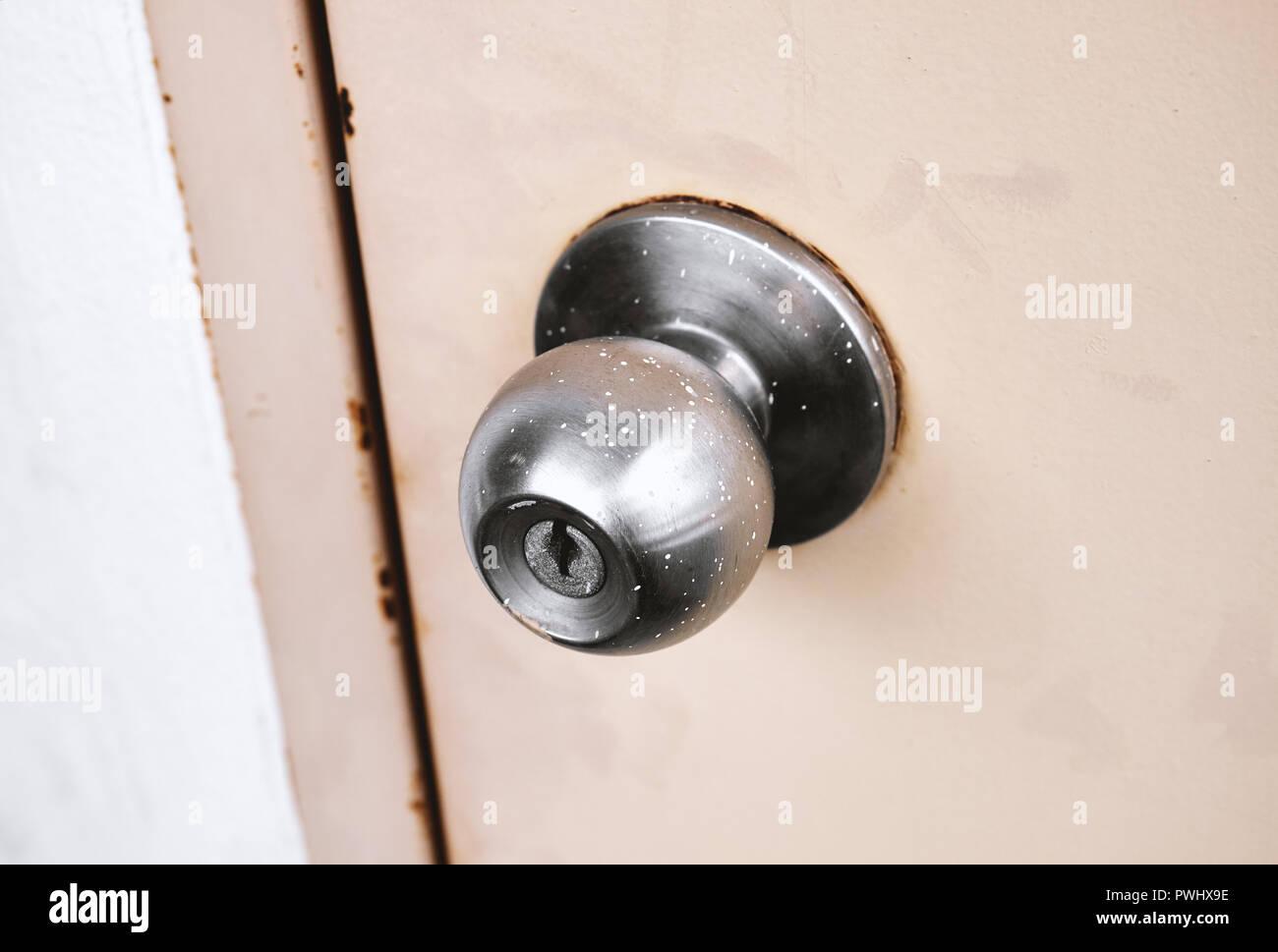 Old rusty stainless steel knob door on fire exit emergency door. - Stock Image