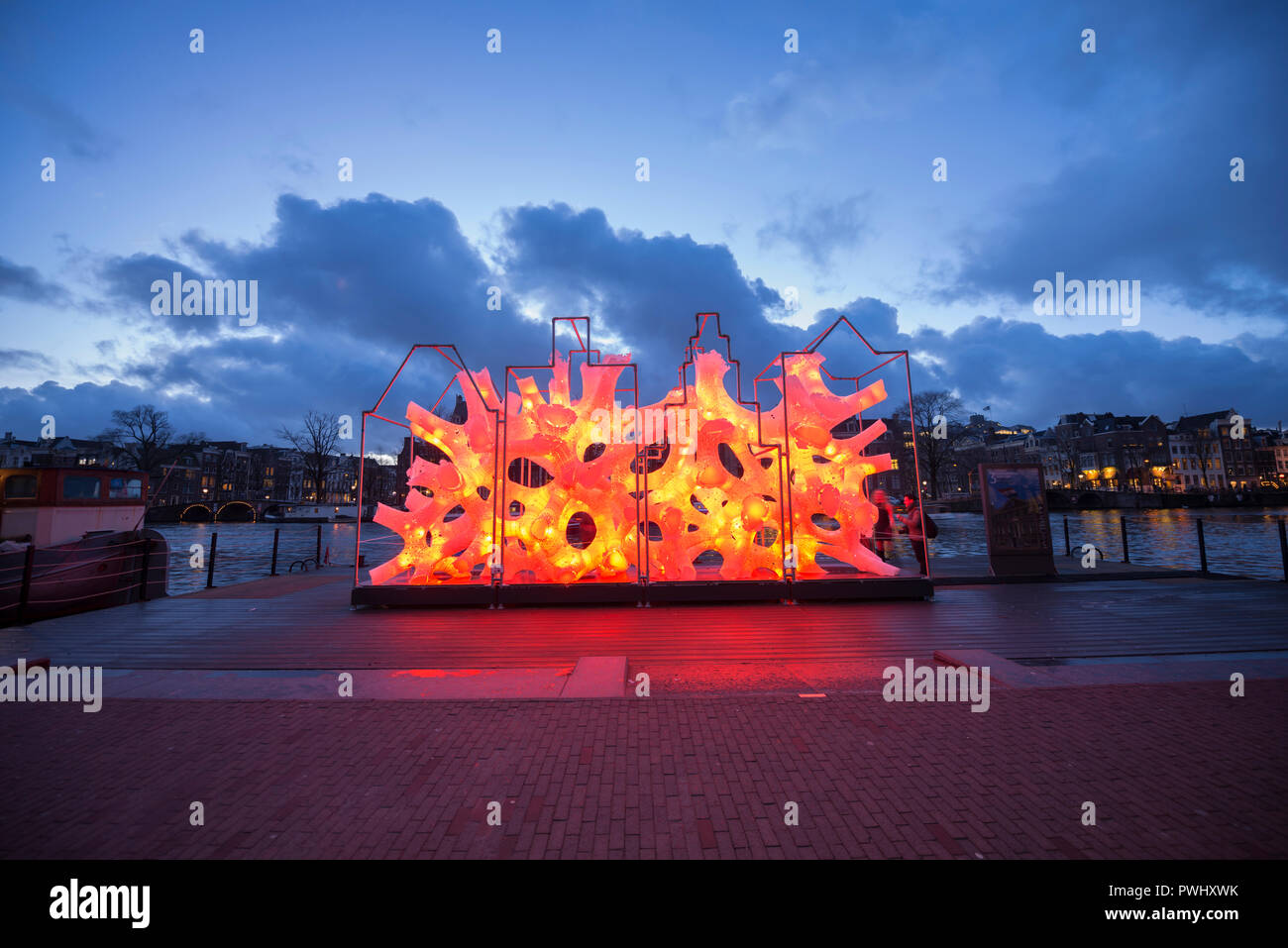 "Amsterdam during Amsterdam Light Festival with color changing artwork ""Rhizome House""in red orange of ""DP Architects"" with beautiful sky, river Amstel Stock Photo"