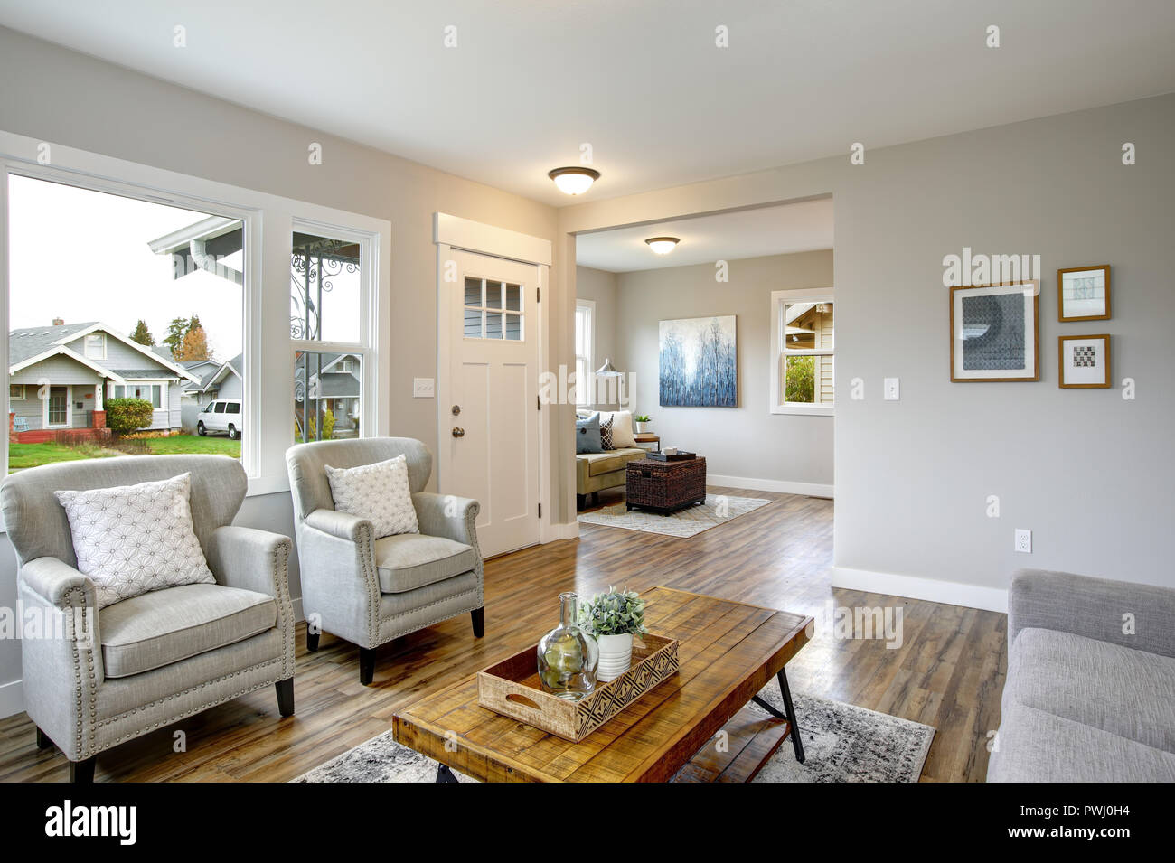 Spacious living room with light gray walls and large window ...