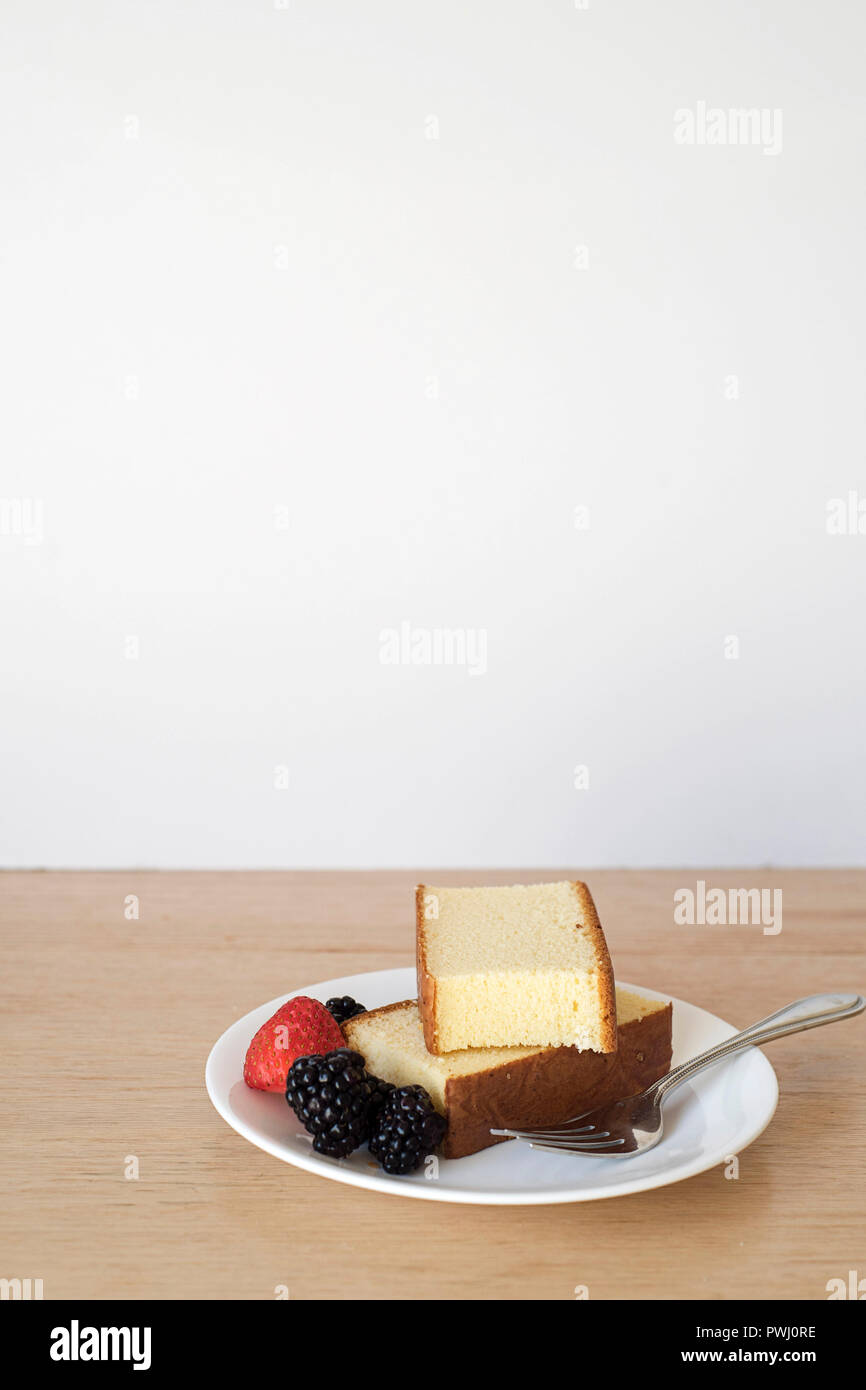 Wide Shot of Loaf Cake Slices Served on a While Plate in Front of a Light Background vertical - Stock Image