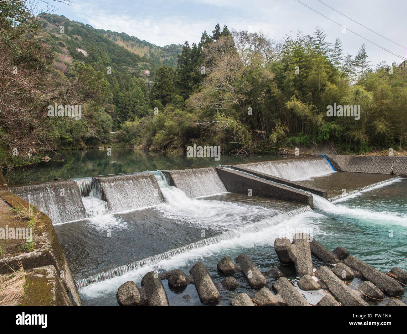 River management, a weir shaping river flow, with tetrapods below, Iyoki River, Koch, Shikoku, Japan - Stock Image