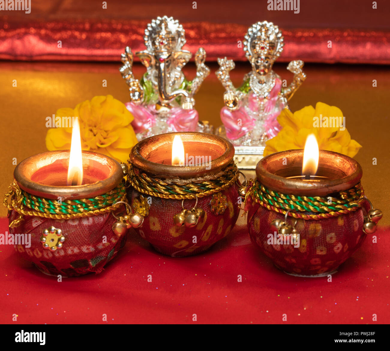Diwali Background Showing Lit Lamps Against Hindu Idols of Deities Lakshmi and Ganesh Stock Photo