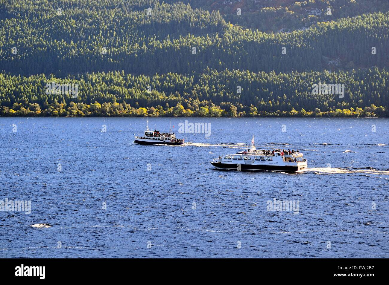 Drumnadrochit, Scotland, United Kingdom. A pair of tourist boats negotiating the waters of Loch Ness within the Scottish Highlands. - Stock Image