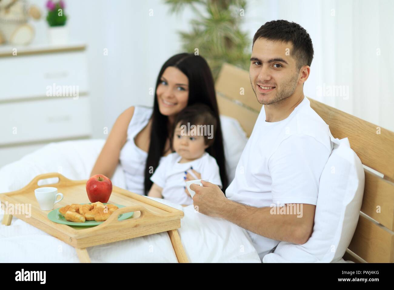 Family having breakfast in bed at home - Stock Image