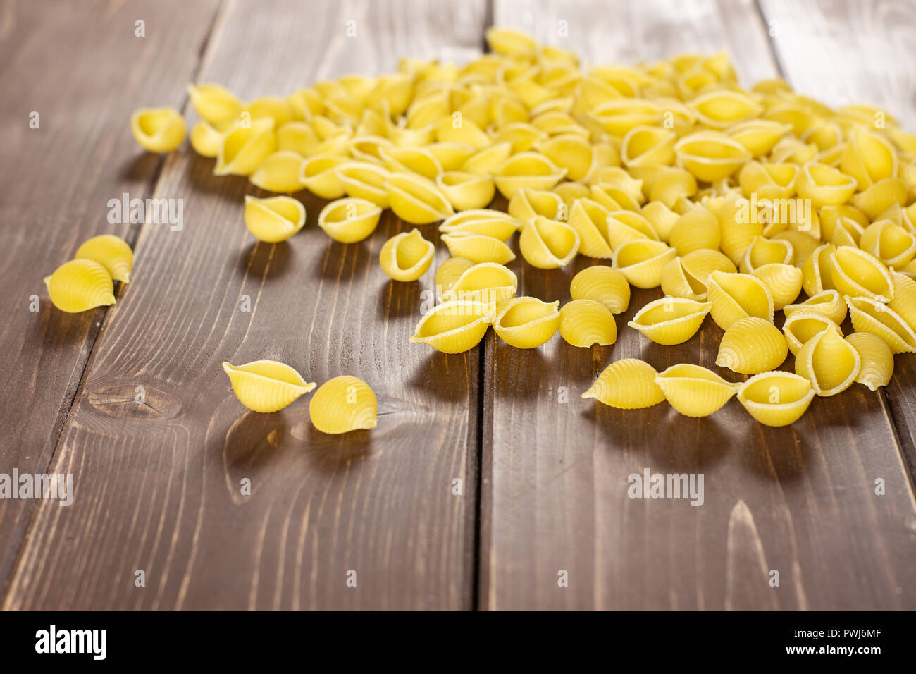 Lot of whole raw yellow pasta conchiglie variety on brown wood Stock Photo