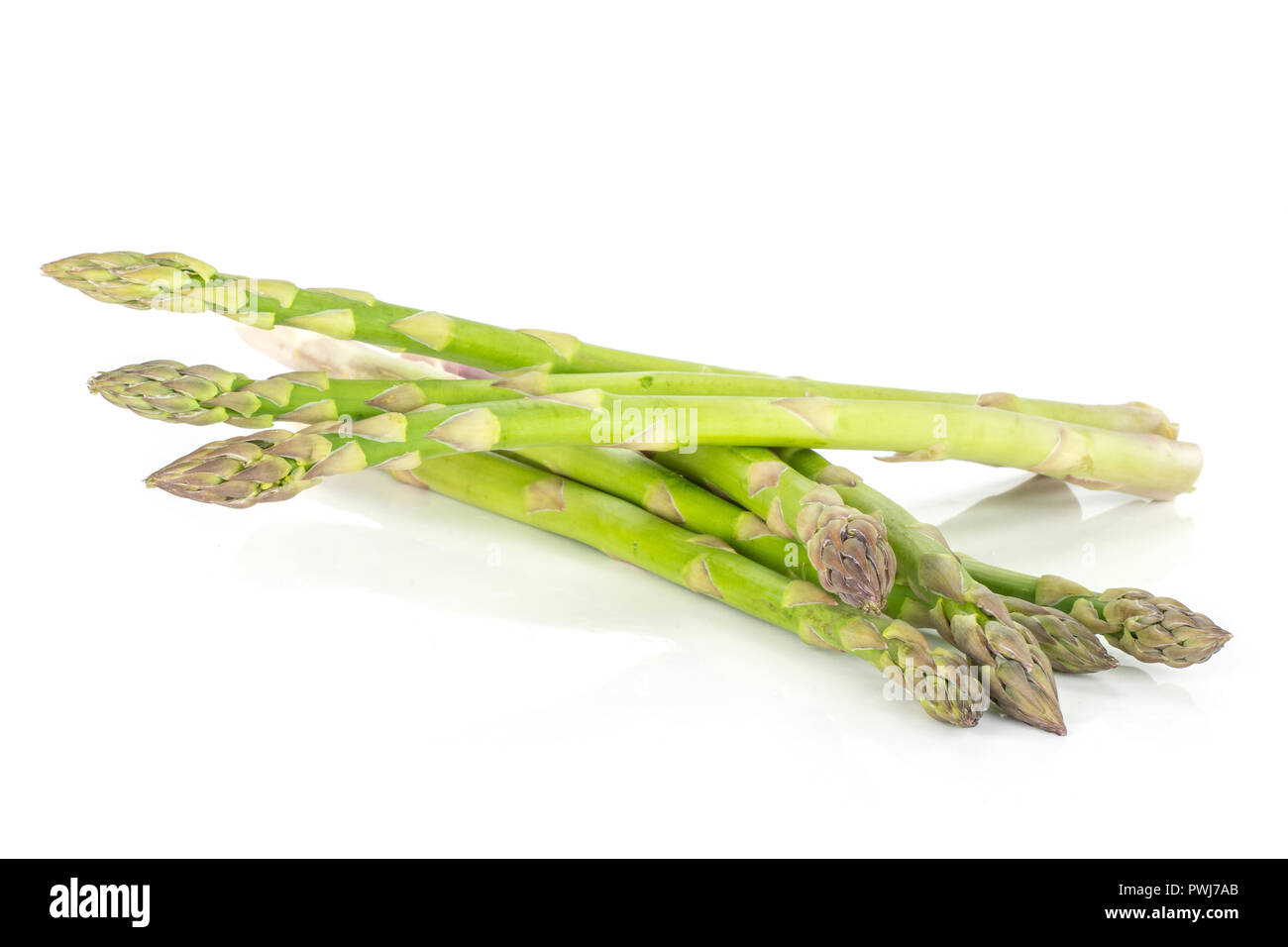 Lot of whole scaly fresh green asparagus spear isolated on white background - Stock Image