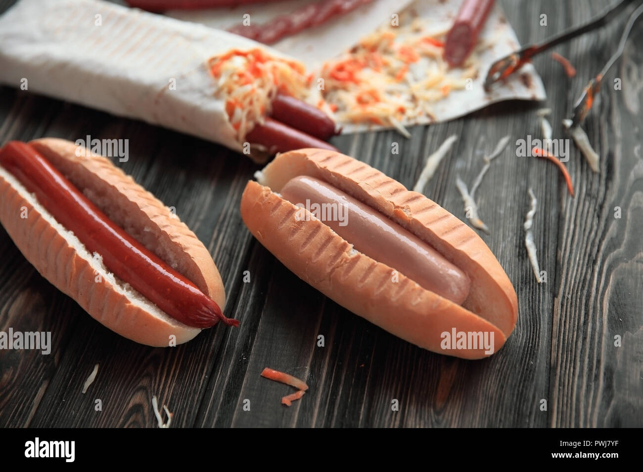 preparation of hot dogs with sausage.photo on a wooden backgroun - Stock Image