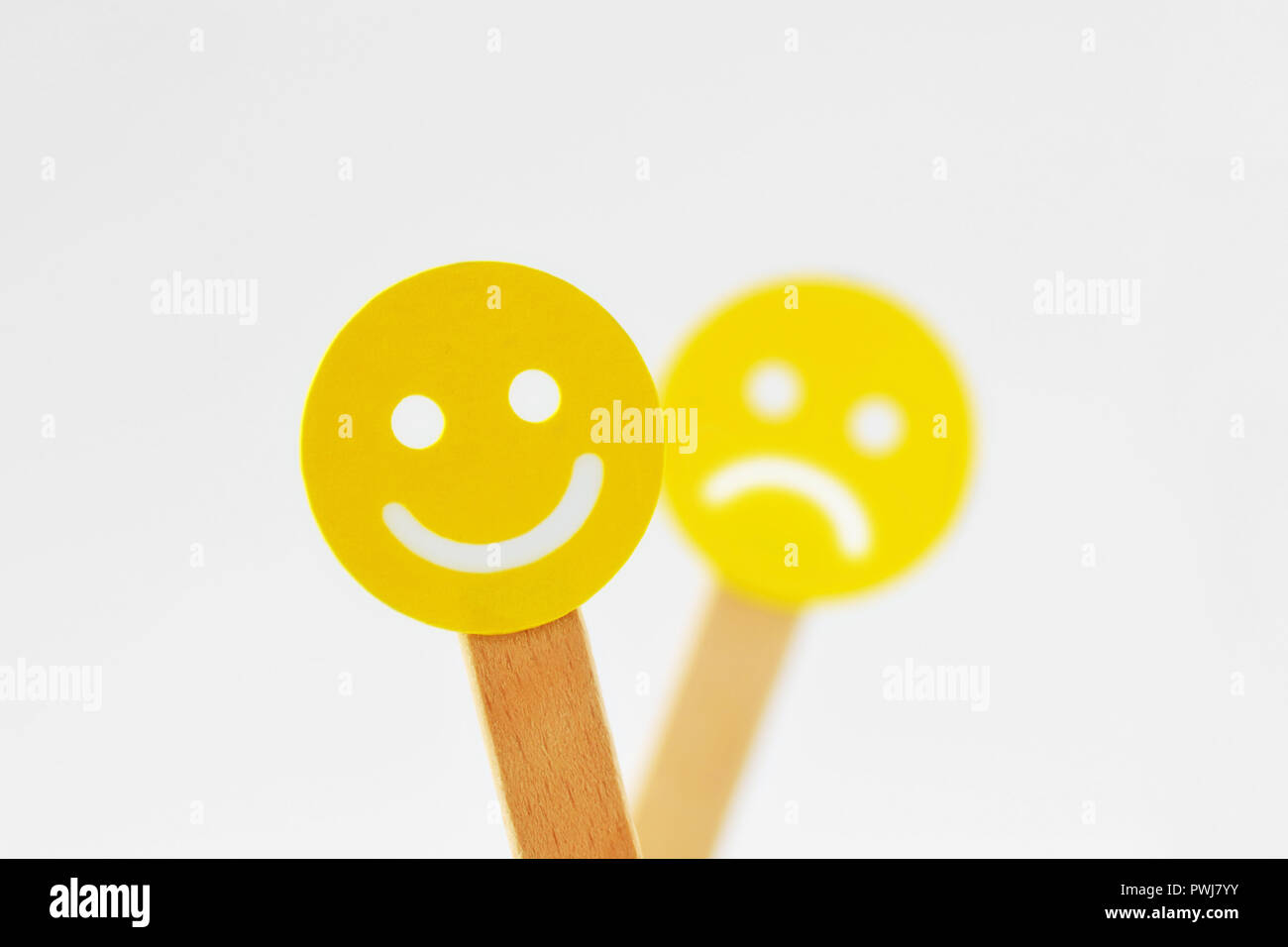 Smiley face with positive expression in front of out of foucs sad face - Positivity concept