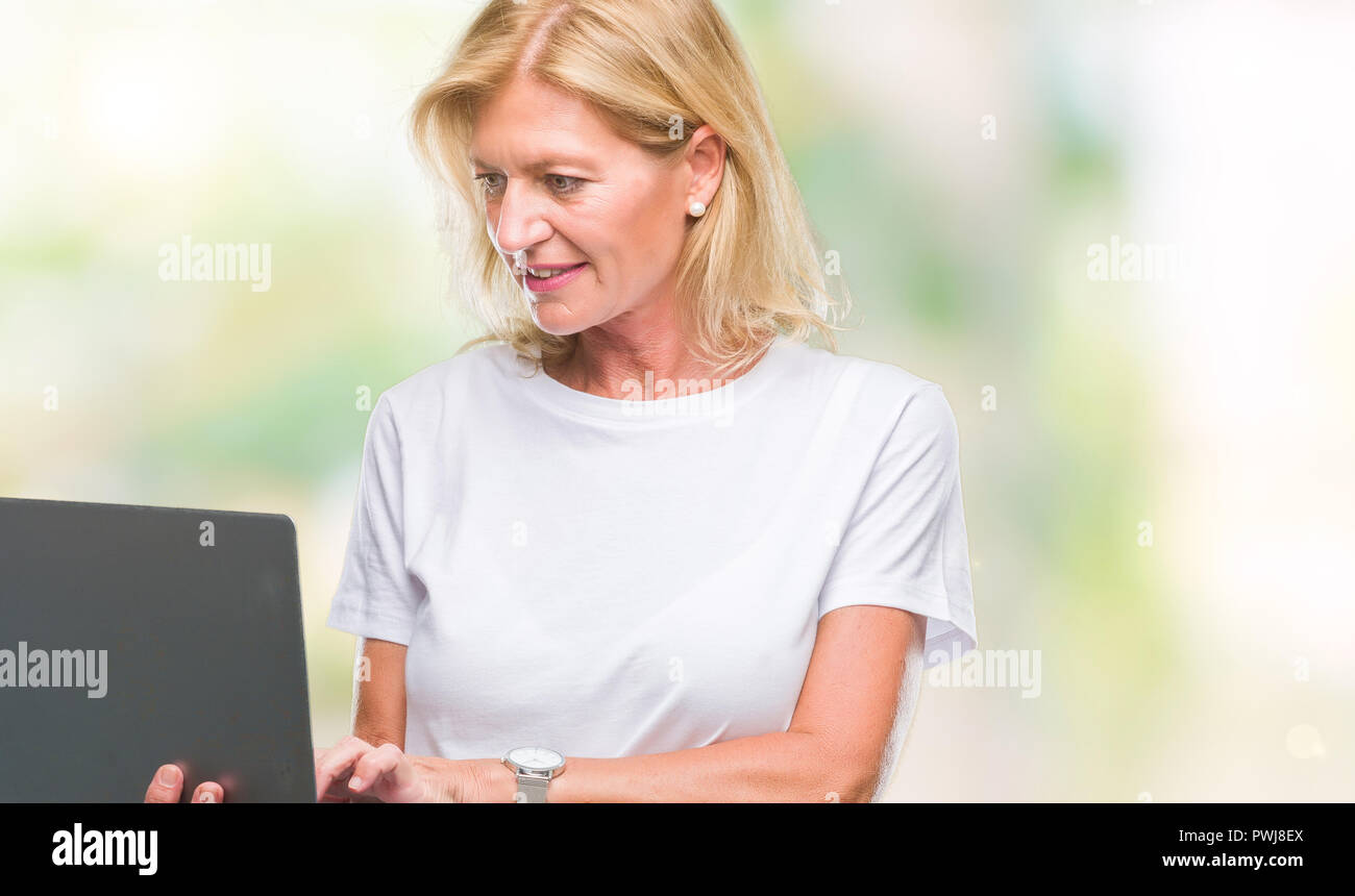 Middle age blonde woman using computer laptop over isolated background with a confident expression on smart face thinking serious Stock Photo
