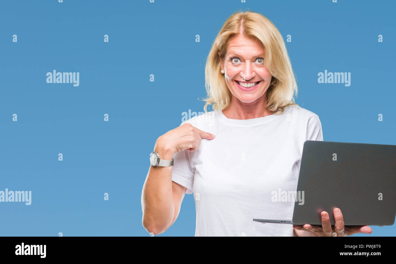 Middle age blonde woman using computer laptop over isolated background with surprise face pointing finger to himself Stock Photo