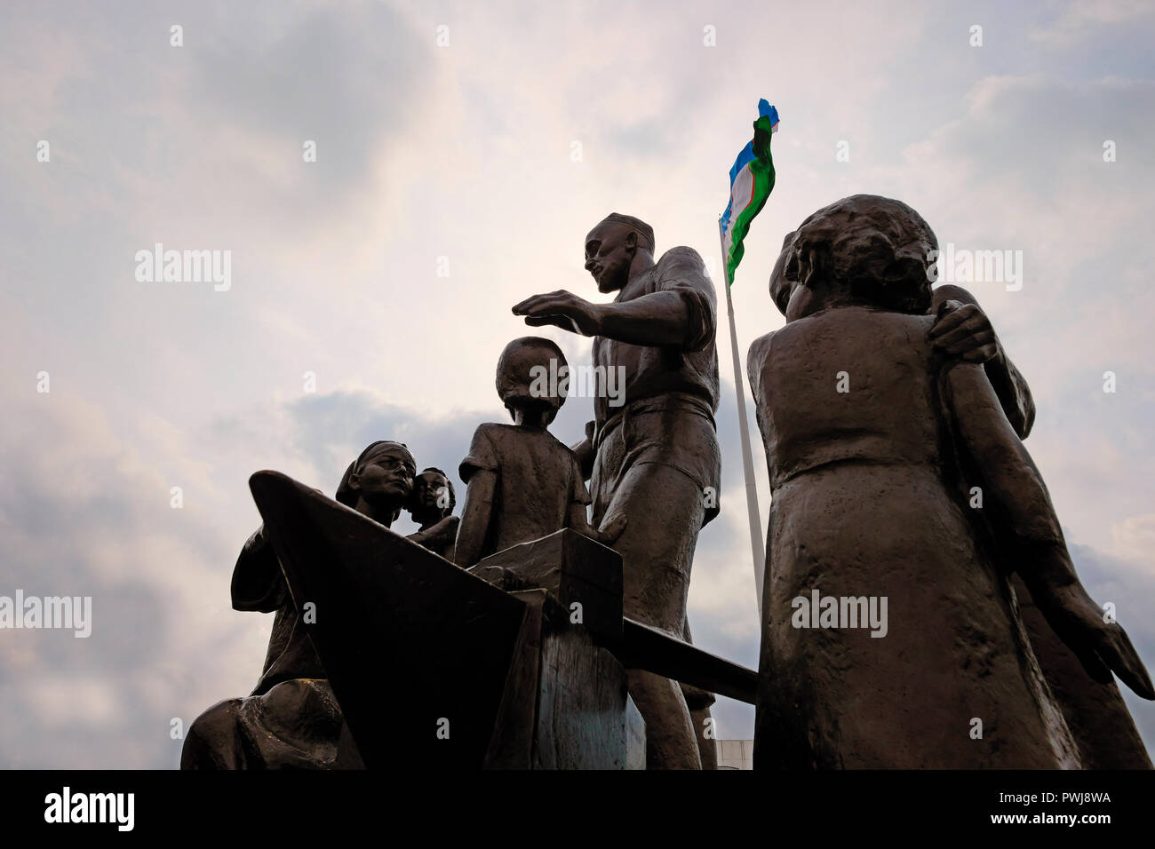 The Uzbek national flag flutters over a Soviet-era monument (created by sculptor Dmitry Ryabichev in 1982) to the blacksmith Shaakhmed Shamakhmudov and his wife Bahri Akramova who adopted 15 children of different nationalities, who lost their parents and were evacuated to Tashkent during WWII placed at the Park of Amity in Tashkent, capital of Uzbekistan. During Second World War more than one million evacuees, including more than 200,000 children who had lost their parents, were moved to Uzbekistan. Every day, between 200 and 400 orphans arrived at Tashkent railway station. - Stock Image