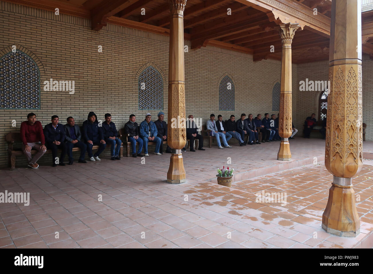 Muslim worshipers sitting at the courtyard of the structure reputedly holding the remains of the Old Testament prophet Daniel, revered by Muslims, Jews and Christians alike in the city of Samarkand alternatively Samarqand of the Timurid dynasty in Uzbekistan - Stock Image