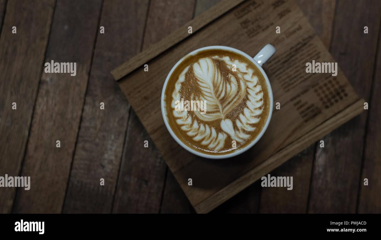 Nice shape of latte art coffee serve on wooden plate - Stock Image