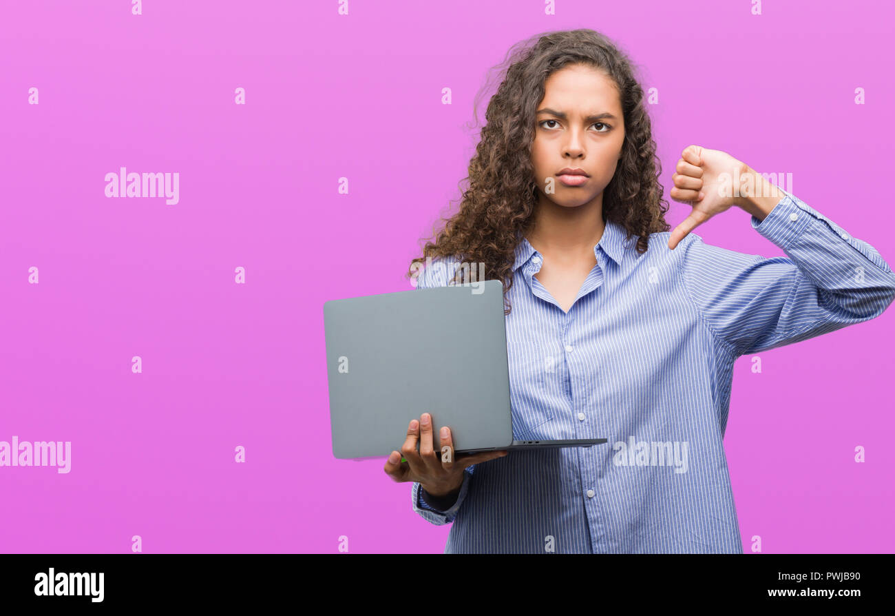 Young hispanic woman holding computer laptop with angry face, negative sign showing dislike with thumbs down, rejection concept - Stock Image