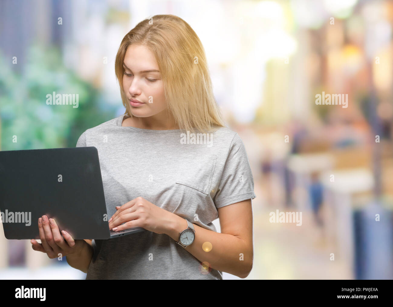 Young caucasian woman using computer laptop over isolated background with a confident expression on smart face thinking serious - Stock Image