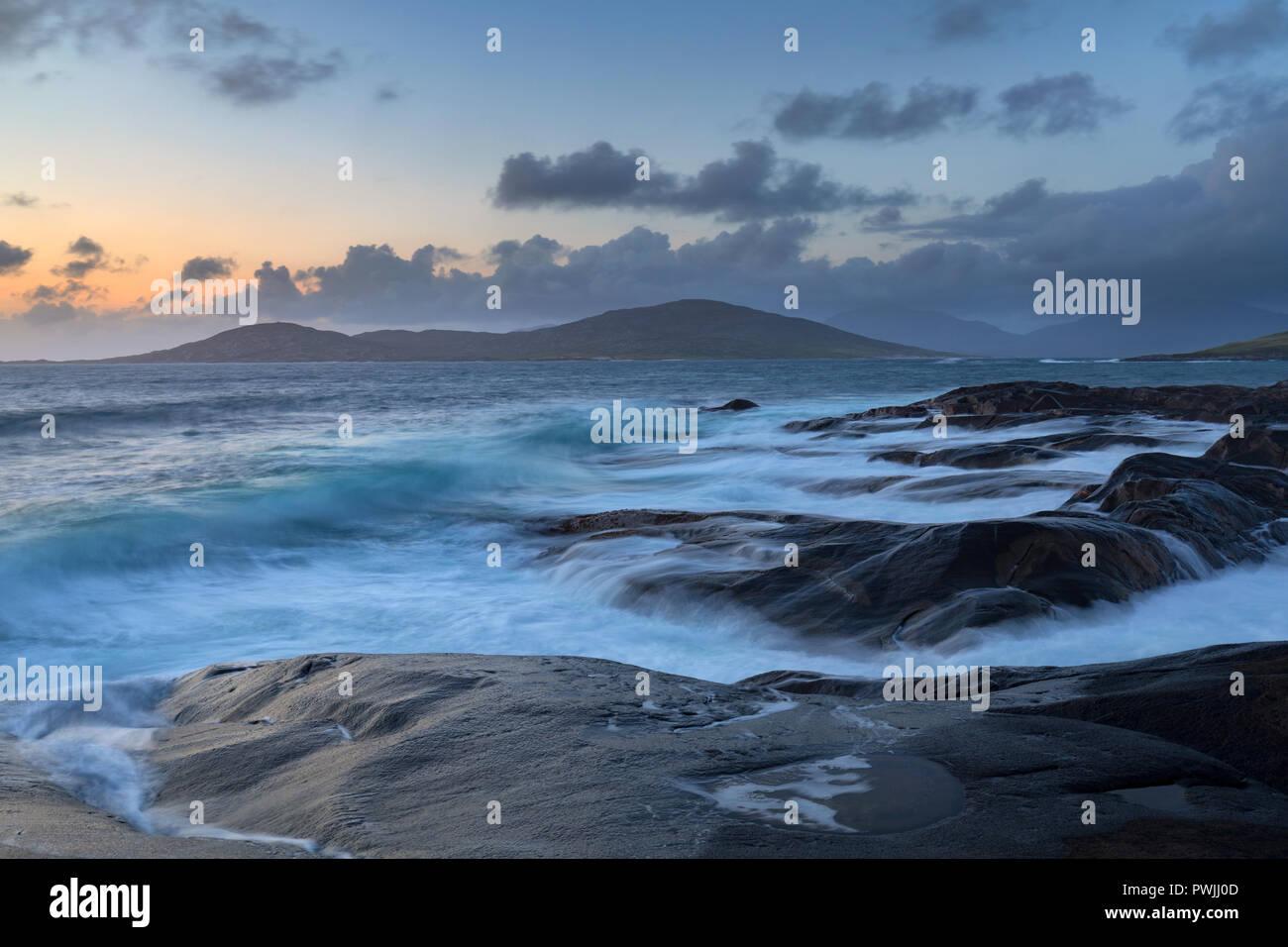 Waves crashing on the shore of Harris looking across to Isle of Taransay - Stock Image