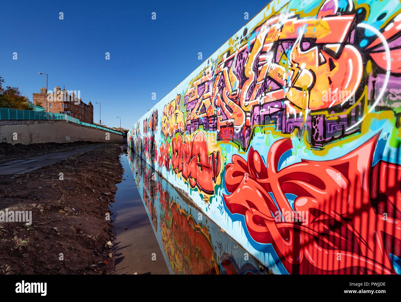 View of murals painted on wall at Marine Parade Graffiti Wall in Leith , Scotland, - Stock Image