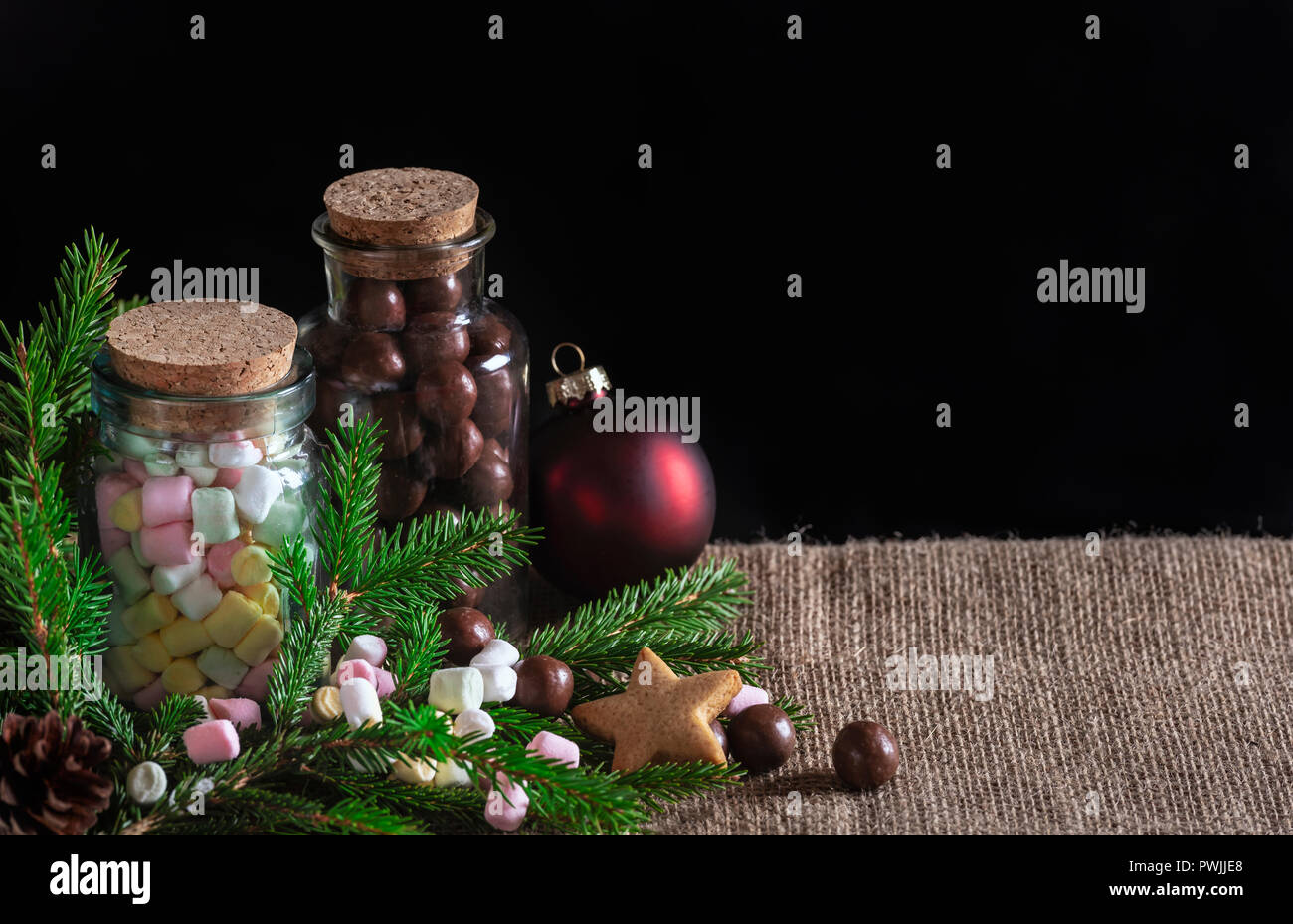 christmas treats banner with bottles full of multi colored mini marshmallows and chocolate candies green fir twigs and xmas ball on jute fabric