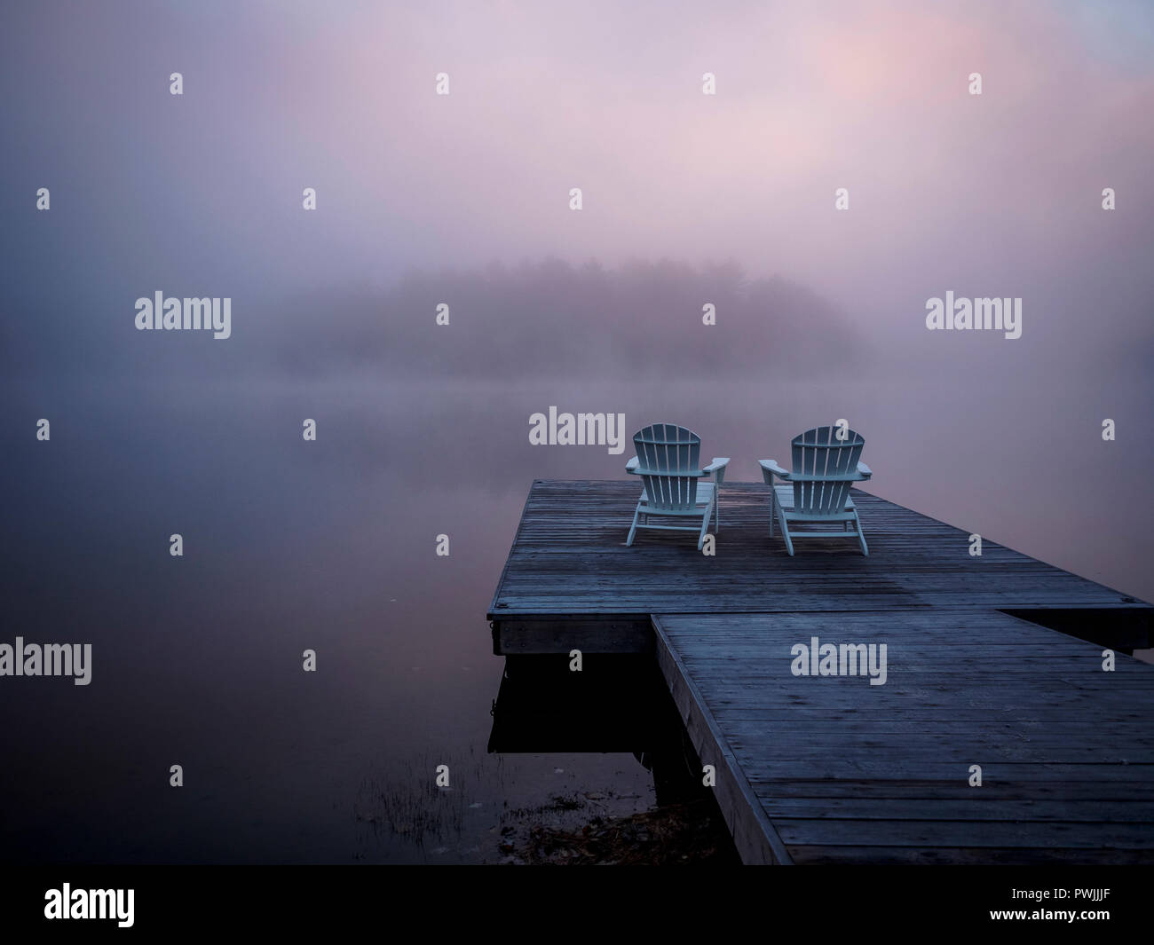 Two Muskoka Chairs in front of lake Benoir, Ontario on a wooden dock. A really foggy day on early morning with light pink & orange haze due to sunrise - Stock Image