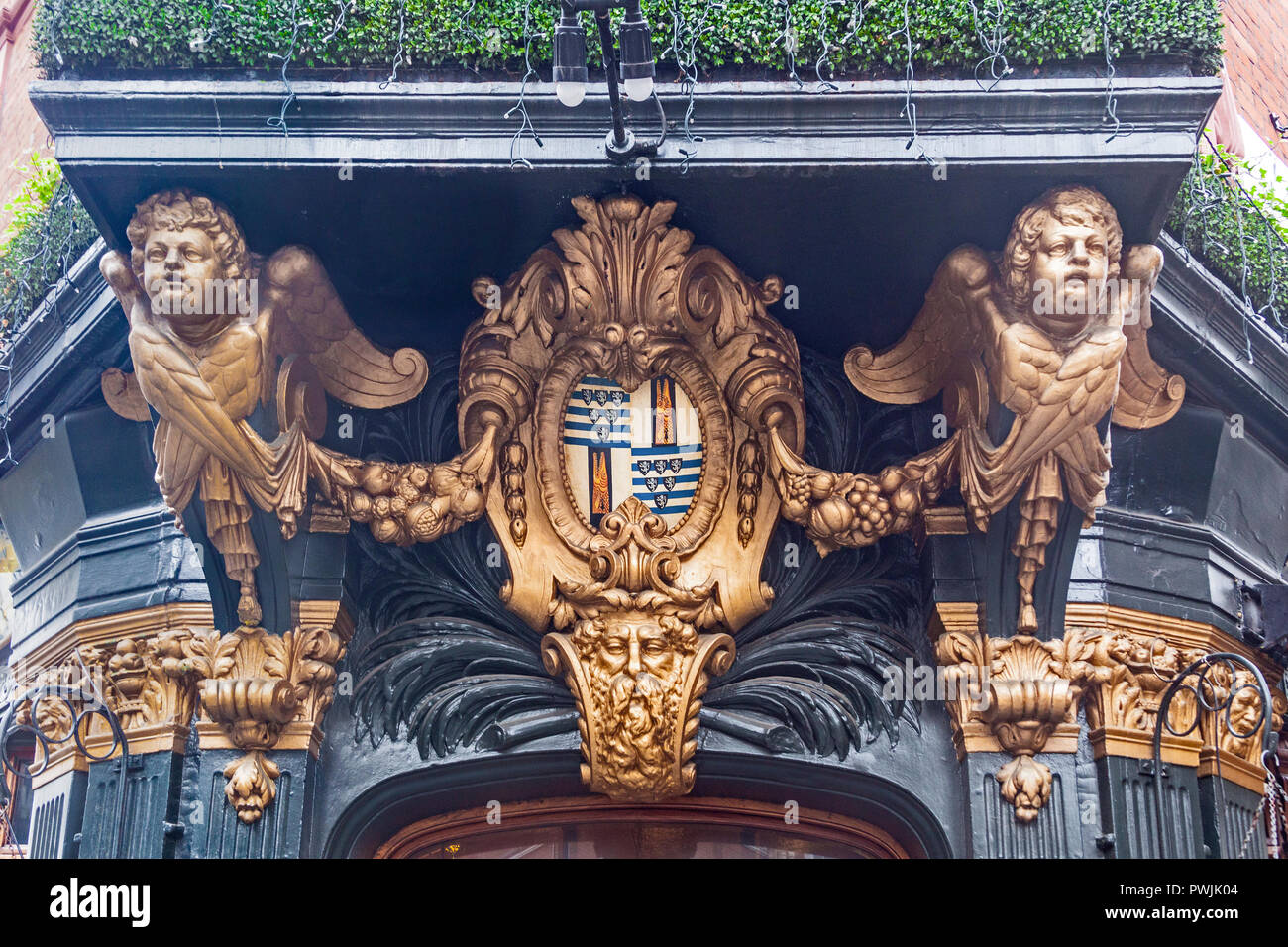 London, City of Westminster.   A pair of angelic figures supporting a canopy over the entrance to The Salisbury public house in St Martin's Lane. - Stock Image