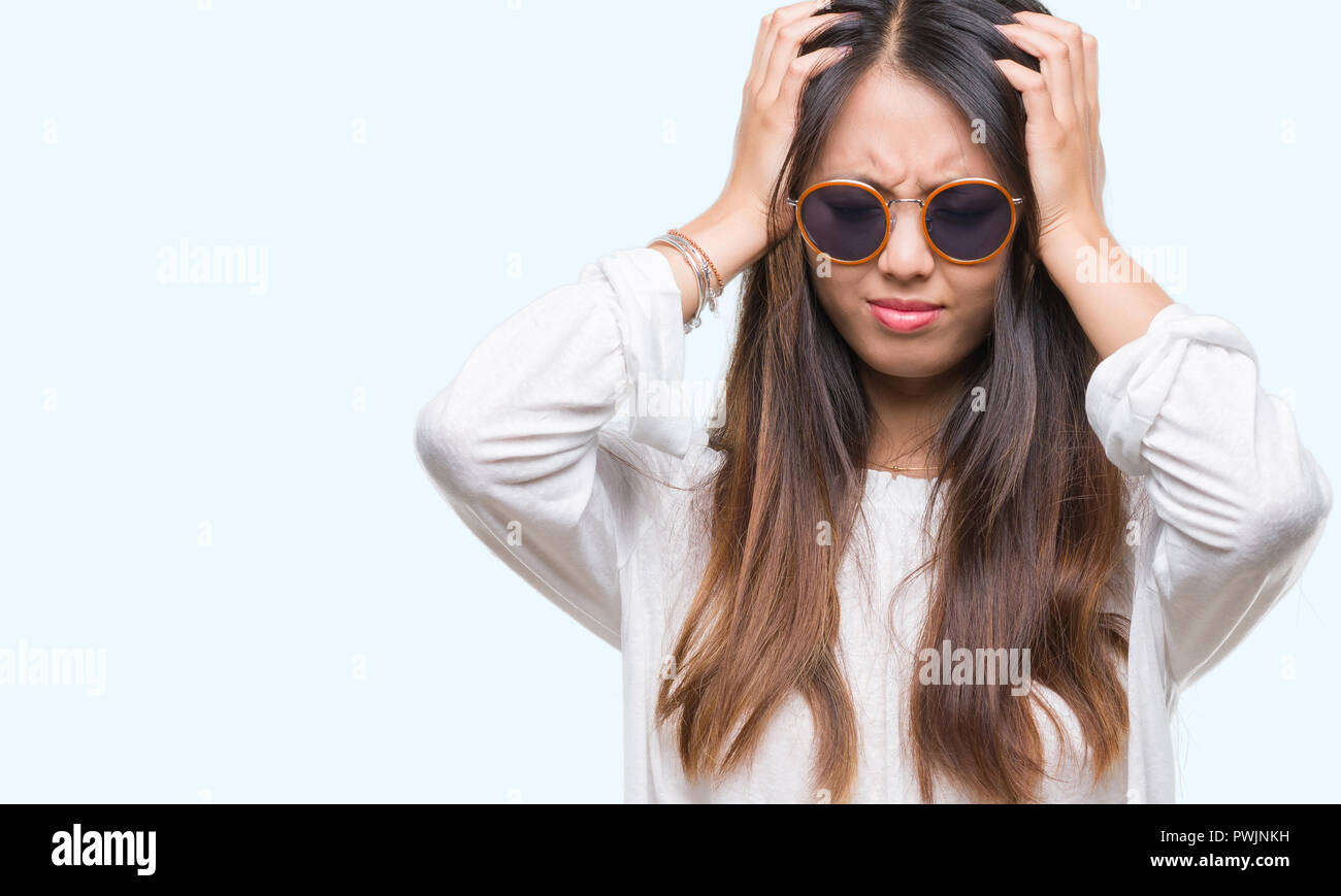 96311e5ca46 Young asian woman wearing sunglasses over isolated background suffering  from headache desperate and stressed because pain and migraine. Hands on  head.