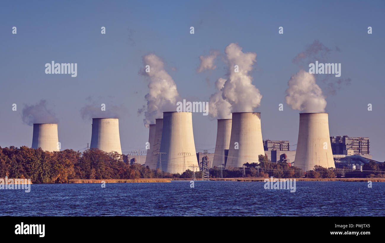 Smoking chimneys next to a lake, environmental pollution concept, color toning applied. Stock Photo