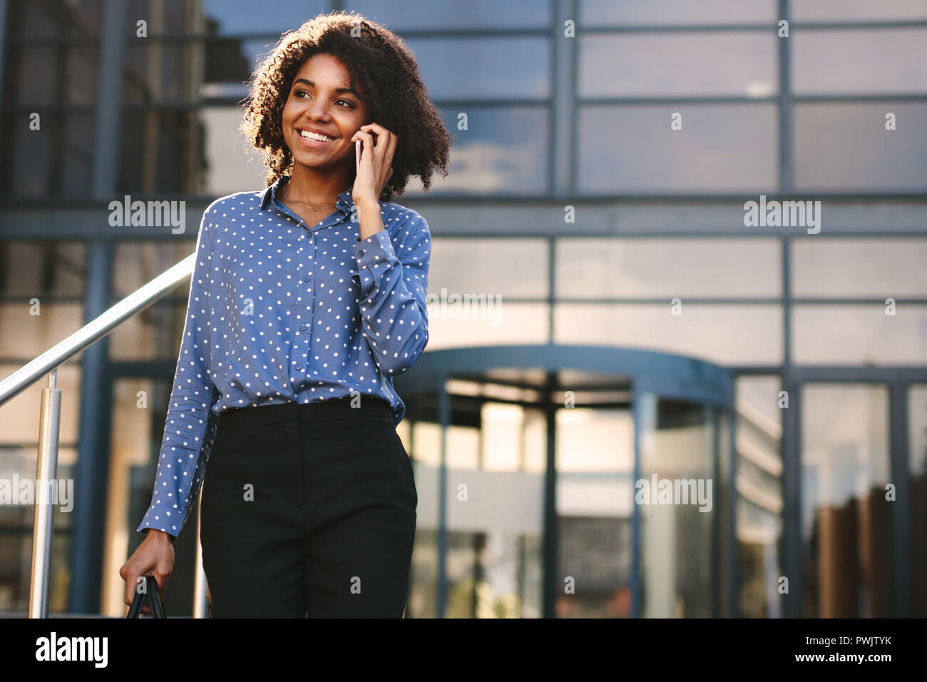 Smiling businesswoman talking over mobile phone while walking outside office building. Woman in formalwear walking outdoors and talking on phone. - Stock Image