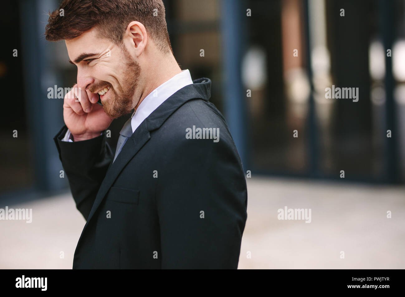 Smiling businessman talking over cell phone. Side view of
