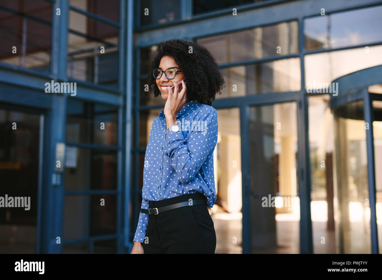 Young businesswoman walking out of the office building talking on mobile phone. Female office worker walking out of the corporate building making a ph - Stock Image