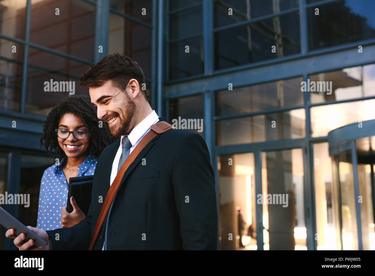 a2748e5e97 Two business colleagues walking out of office building with a digital tablet.  Businessman and woman