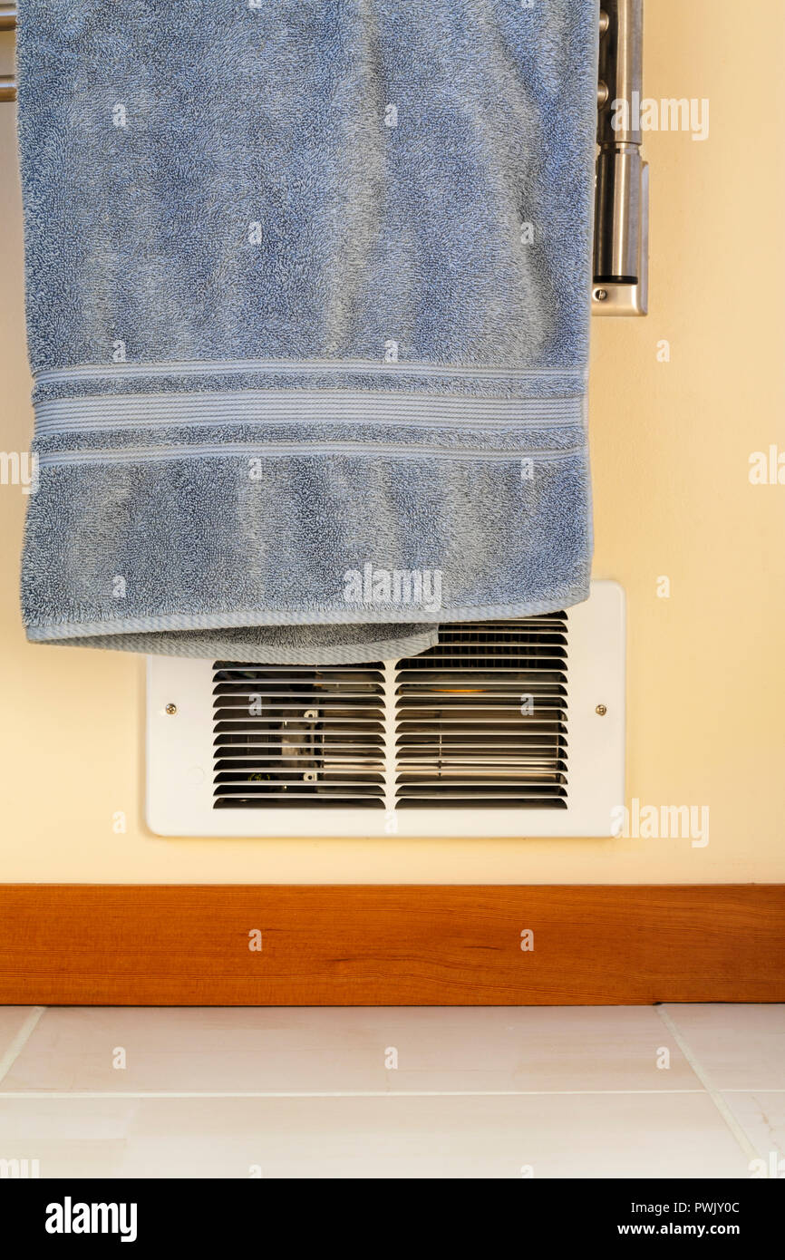 Towel hanging in front of in-wall electric baseboard heater. Dangerous house home fire hazards. - Stock Image
