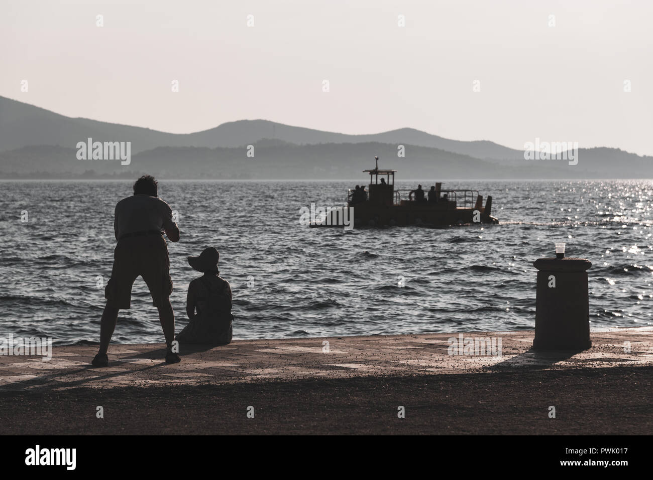 Couple of silhouetted tourists by the sea with a camera muted tones - Stock Image