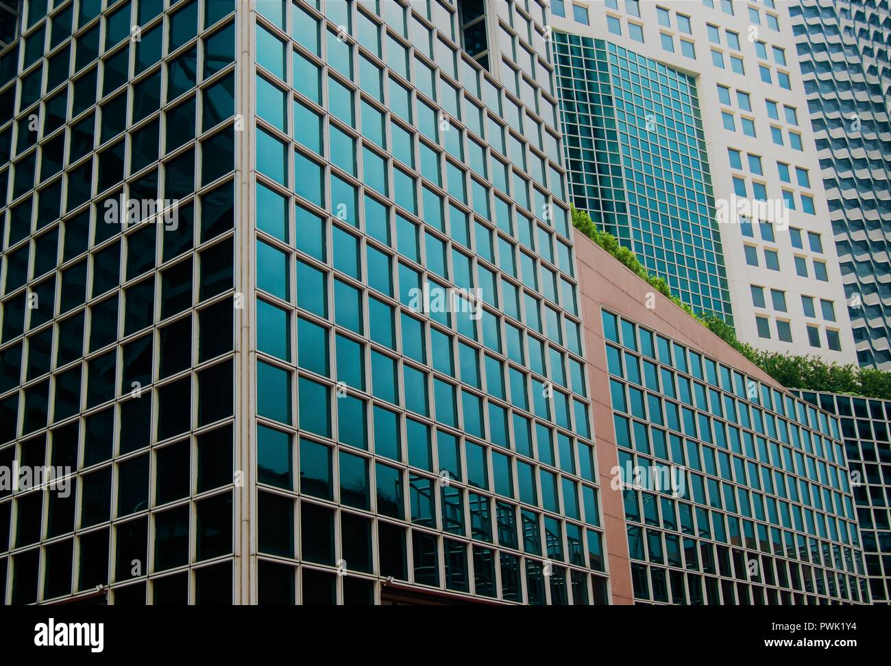 871cc7777af Abstract glass exterior of modern office buildings in downtown Singapore  with symmetrical patterns