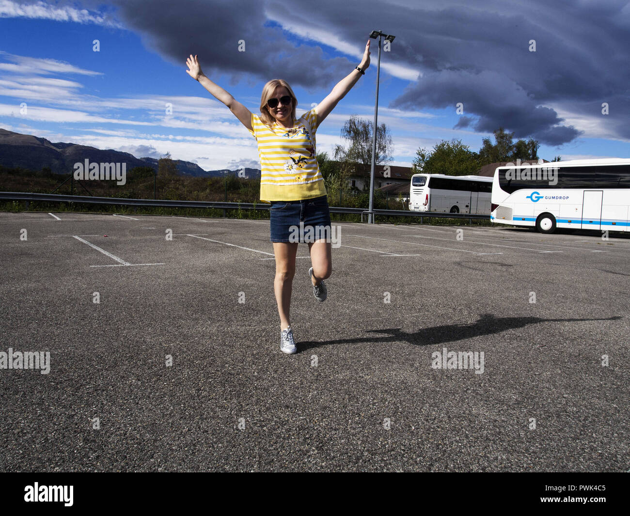 September 22, 2018 - Ferney-Voltaire, France - A woman seen jumping in joy on the parking next to Hotel F1. Hotel Formule 1, or hotelF1 in France, is an international chain of ''super low budget'' or ''no frills'' hotels owned by AccorHotels. Credit: Igor Golovniov/SOPA Images/ZUMA Wire/Alamy Live News - Stock Image