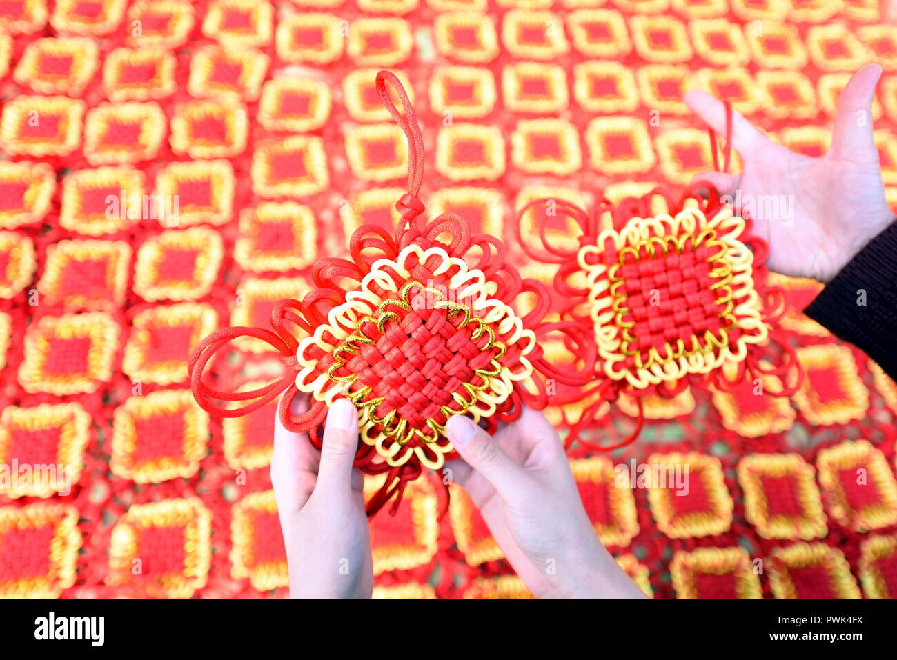 Linyi, Linyi, China. 16th Oct, 2018. Linyi, CHINA-The Chinese knotting manufacturing industry booms in Shancheng County, Linyi, east China's Shandong Province.Chinese knotting is a decorative handicraft art that began as a form of Chinese folk art in the Tang and Song dynasty (960â€'1279 CE) in China. The technique was later popularized in the Ming) and spread to Japan and Korea. Credit: SIPA Asia/ZUMA Wire/Alamy Live News - Stock Image