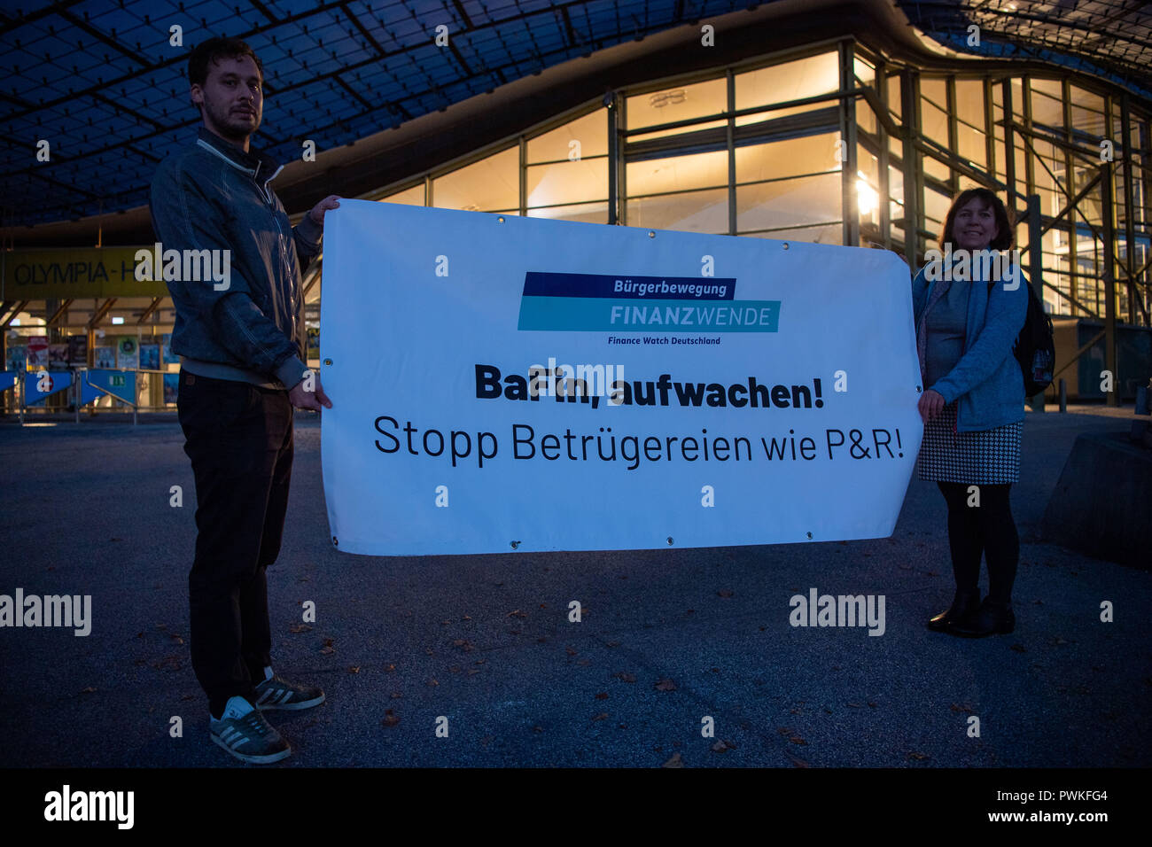 """Munich, Bavaria. 17th Oct, 2018. Demonstrators stand at sunrise at the Olympiahalle in the Olympiapark with a poster of the citizen movement Finanzwende on which it says """"BaFin, wake up! Stop scams like P&R!"""". The damage in the alleged fraud case P&R could lie between one and two billion euros, several thousand creditors are expected for a meeting in the Munich Olympic Hall. Credit: Lino Mirgeler/dpa/Alamy Live News Stock Photo"""
